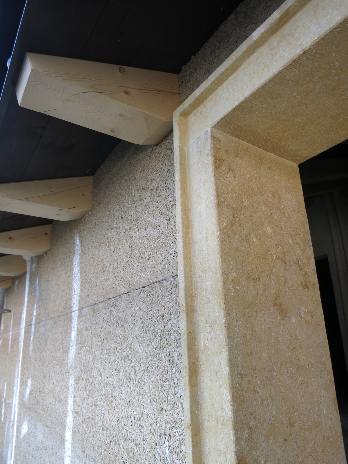 Porzione di muro in NaturalBeton di calce e canapa con cornice in tufo