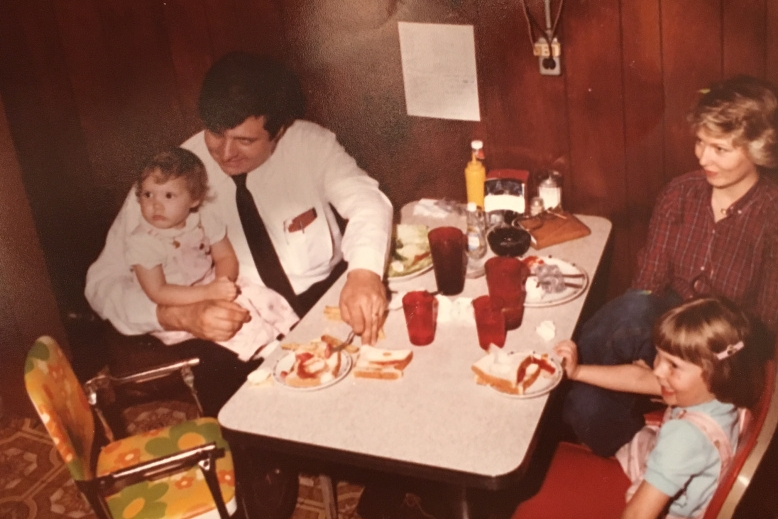 Me and my sister in matching overalls eating with my parents.Check out that floral covered high chair!