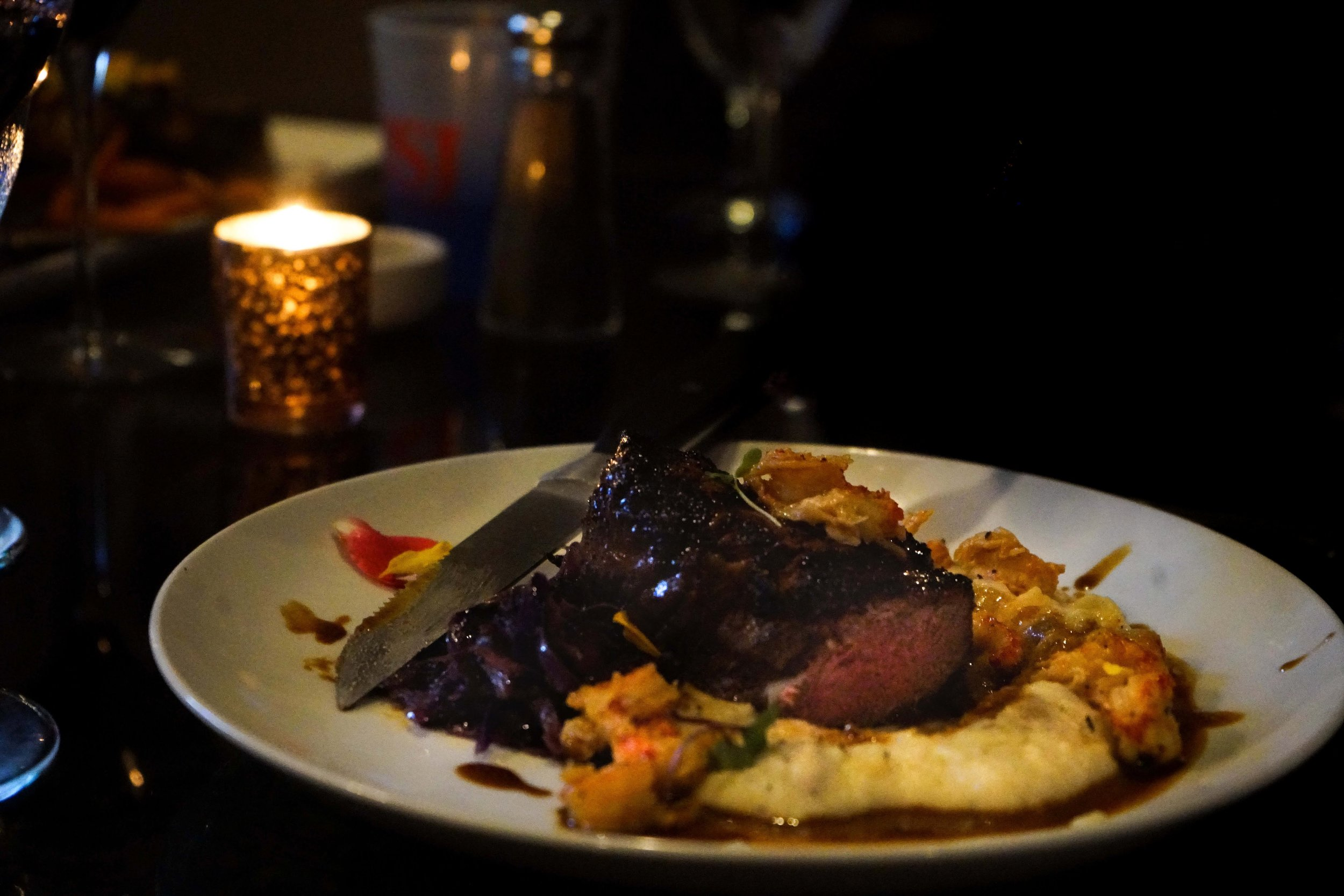 Prime Cut Fillet with Butter Poached Crawfish, Demi-Glace, Sautéed Purple Cabbage, and Mashed Potatoes