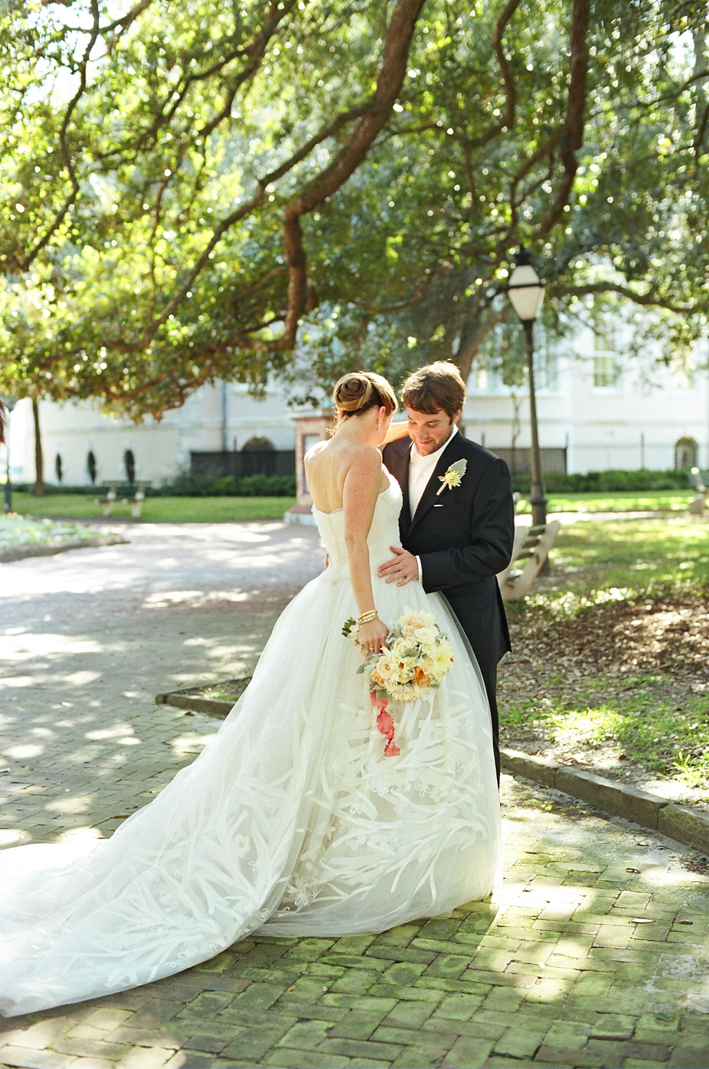 """The bride wore an avant-garde strapless Carolina Herrera gown with layers of tulle that was hand-painted with a branch and blossom motif. Under the layers she positioned a blue bow that served as her """"something blue."""" Photo by Liz Banfield #lizbanfield #historiccharleston #washingtonsquare #firstlook"""