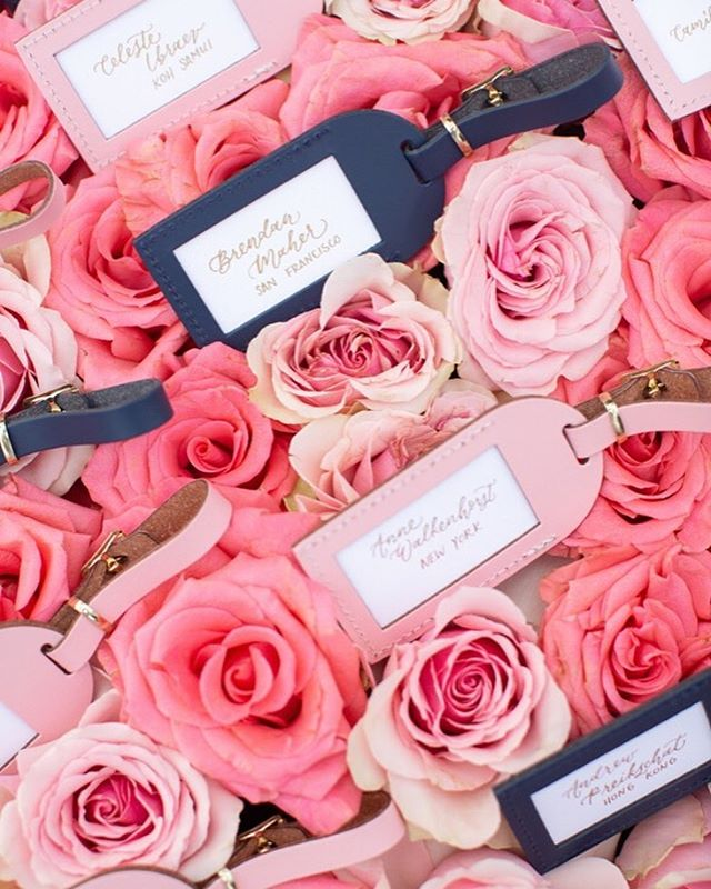 Wedding Details | This couple wanted to share their wanderlust with their guests and so we created custom leather bag tags as escort cards. And of course you can't forget the display, a bed of pink roses was the perfect  place to showcase these gifts. As featured in @stylemepretty | Flowers @sbdesign10 | Photo @brettheidebrecht |