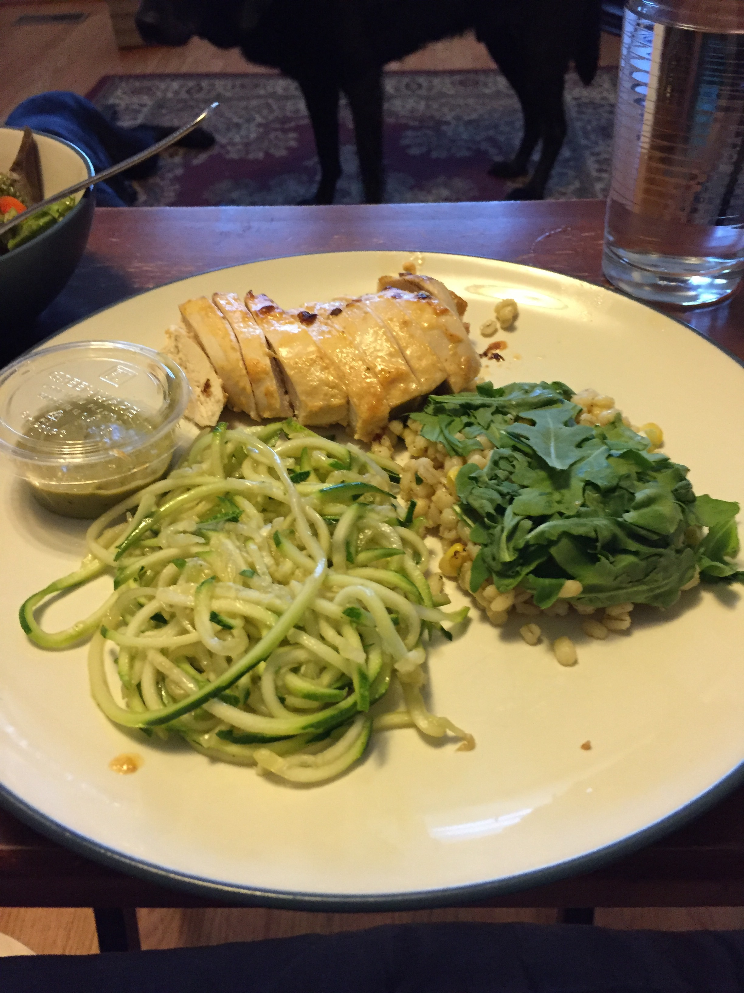 A dinner plate with chicken, barley salad, and zucchini noodles