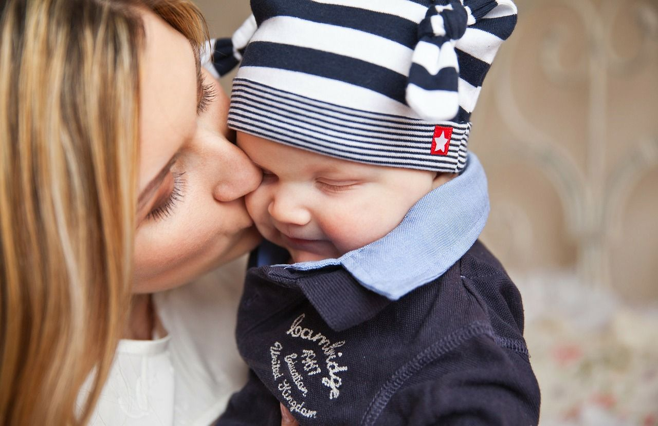 Infant in winter clothes kissed by his mom on cheek Capitol Hill gentle sleep help