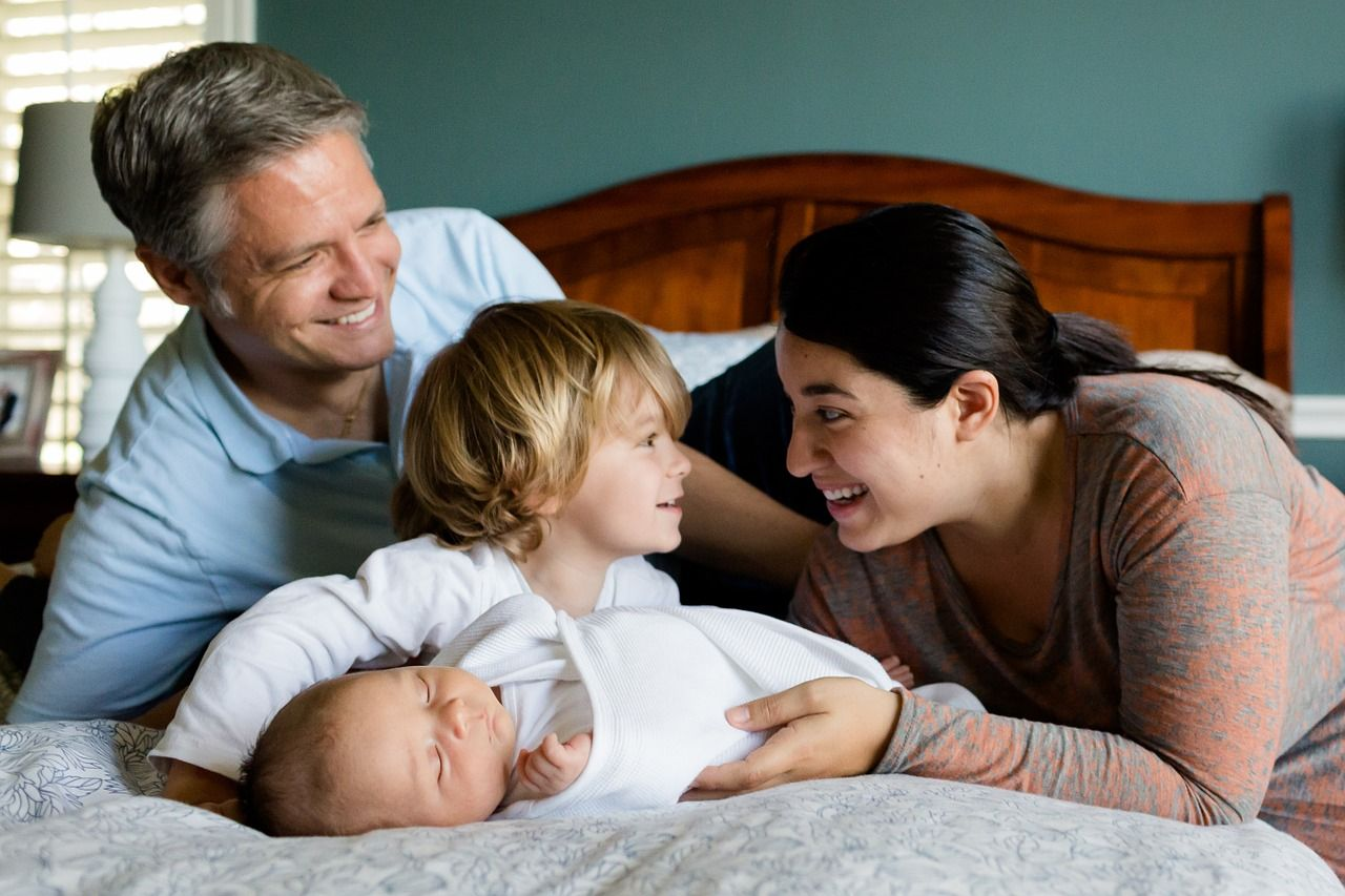 Newborn with family on bed Washington DC bringing baby home classes