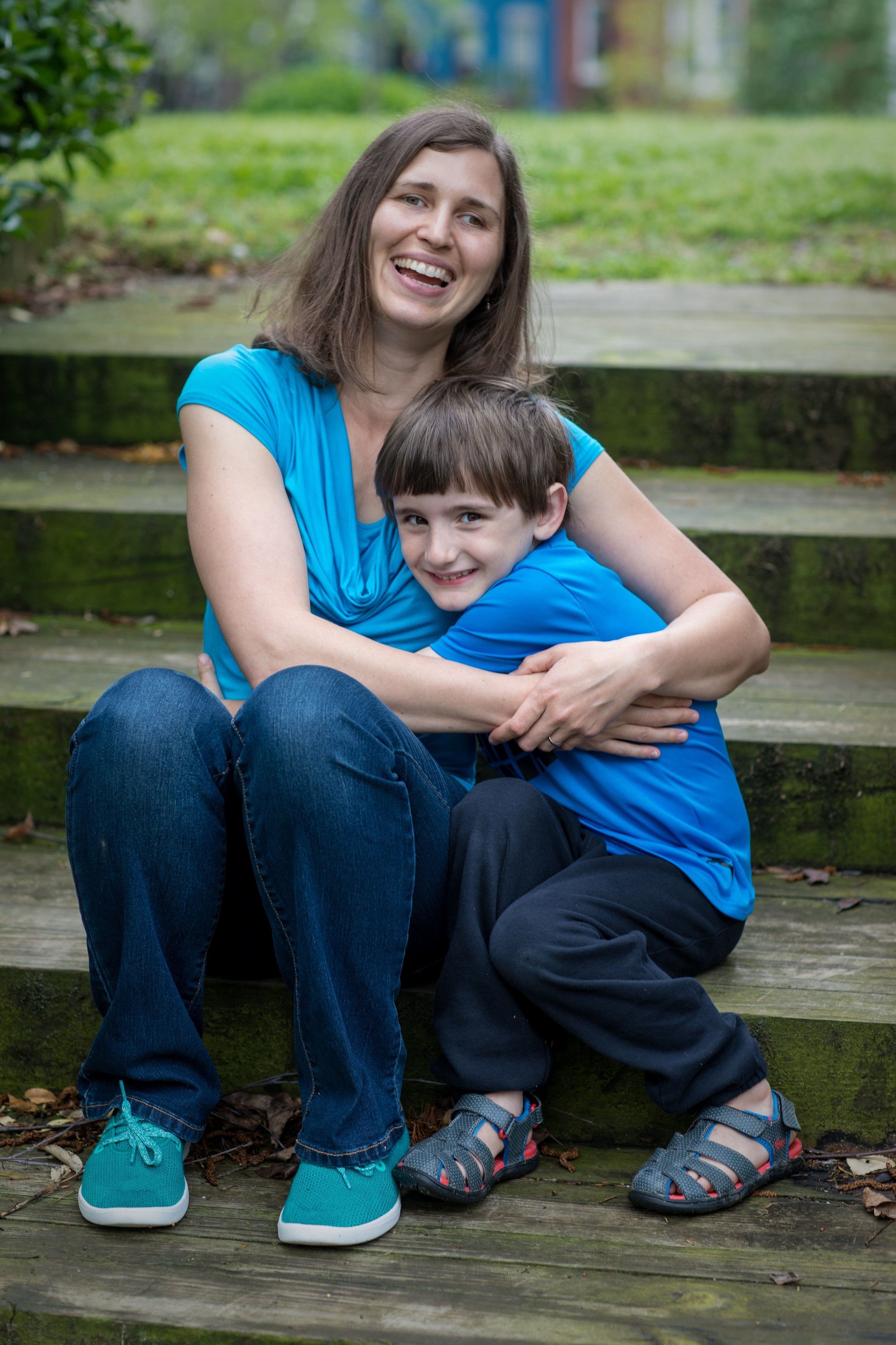 Kim Hawley Gentle Sleep Consultant hugs her son in a park in Capitol Hill