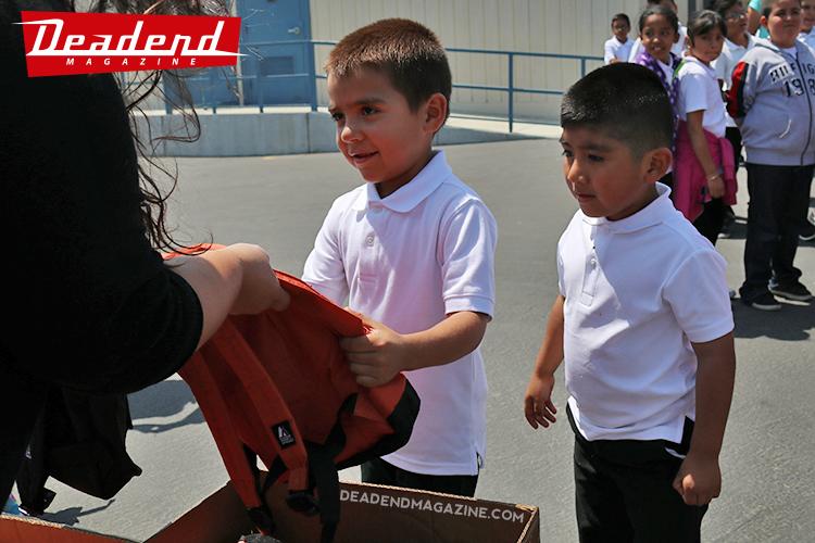 Kindergarten boys picking their backpacks.
