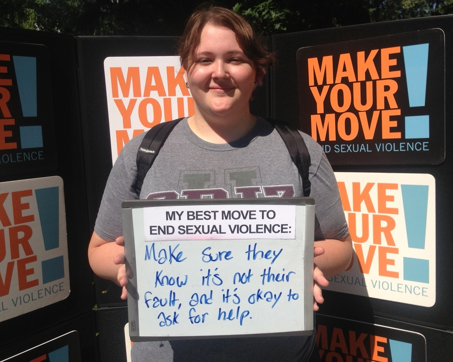 """A person with brown hair holds a whiteboard. The sign says: """"My best move to end sexual violence: Make sure they know it's not their fault, and it's okay to ask for help."""""""