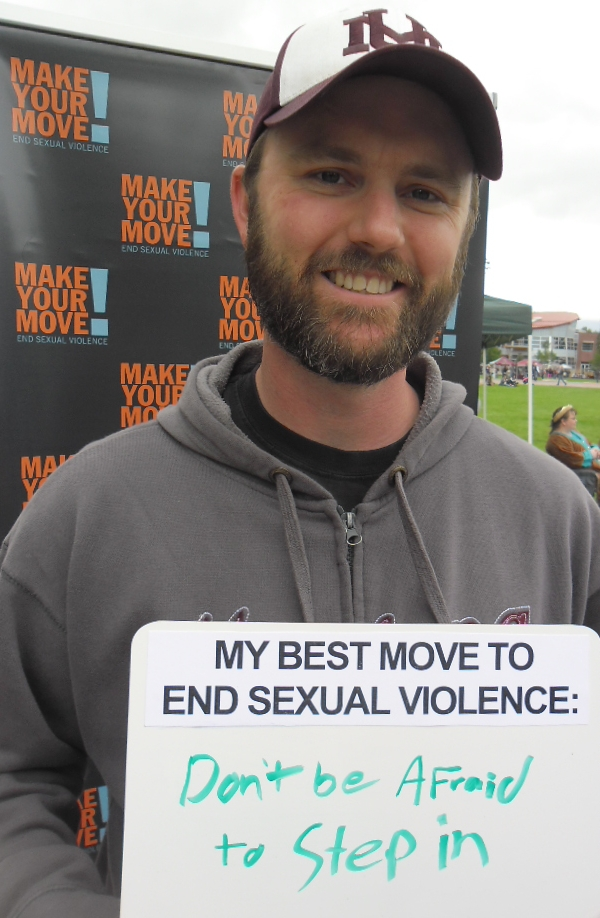 "A man holds a whiteboard that says ""My best move to end sexual violence: Don't be afraid to step in."""
