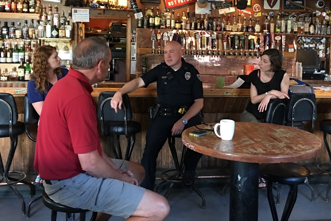 Four people are sitting at a bar, facing one another. The wall of alcohol is behind them. One of the people - a police officer - is talking.