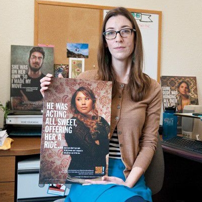 A staff member sits at her desk facing the camera. She holds one of the bystander posters that show a woman intervening on behalf of a friend at the bar.
