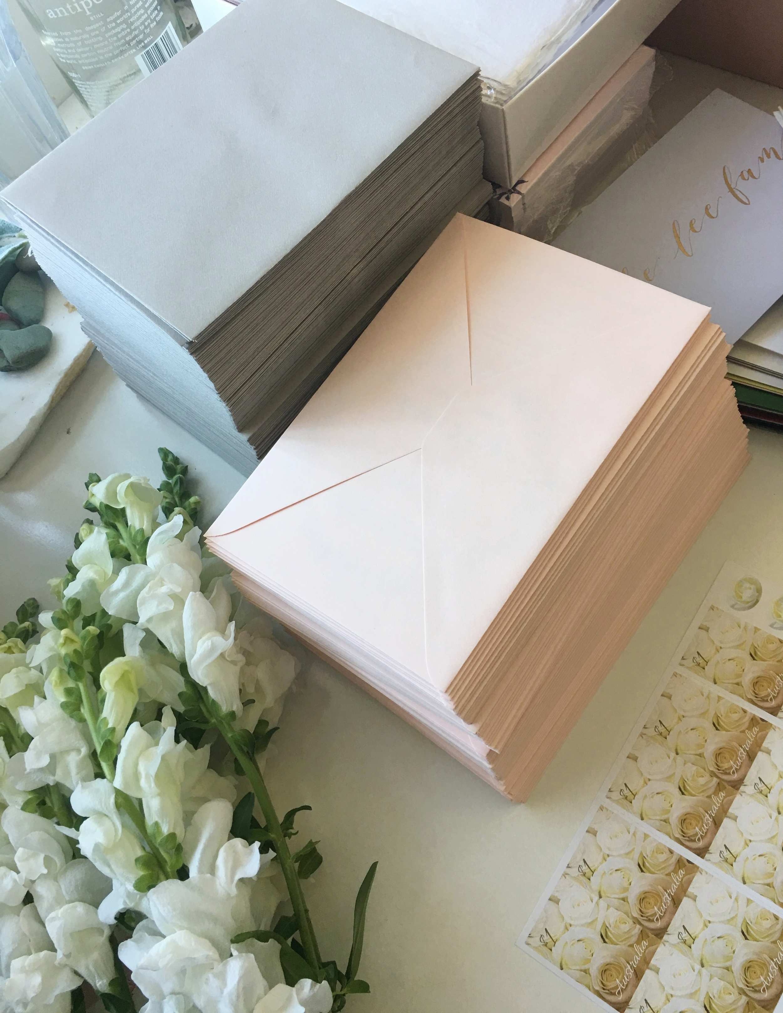 Dove grey and pale blush envelopes with wedding stamps