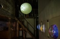 Installation view at artist's studio loft- Photo: Andrew Frost   Top: Videoplanet (2014), video projection onto floating sphere.   Right: PORTALS (2014), acrylic hemispheres, video screens embedded in wooden white finished cases.