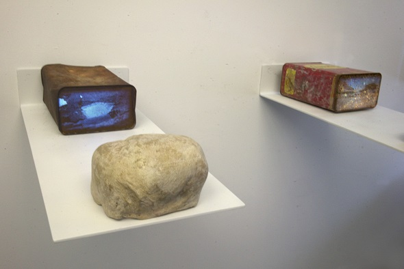 Dana Levy,  Pipelines and Sinkholes,  2019, series of three found one gallon gasoline cans, 04:00 mins single channel videos projected from pico projectors concealed by fake rocks, on 26 x11in (66.04 x 27.94cm) floating shelves