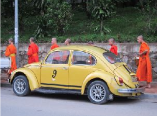 Young Monks passing by a VW bug