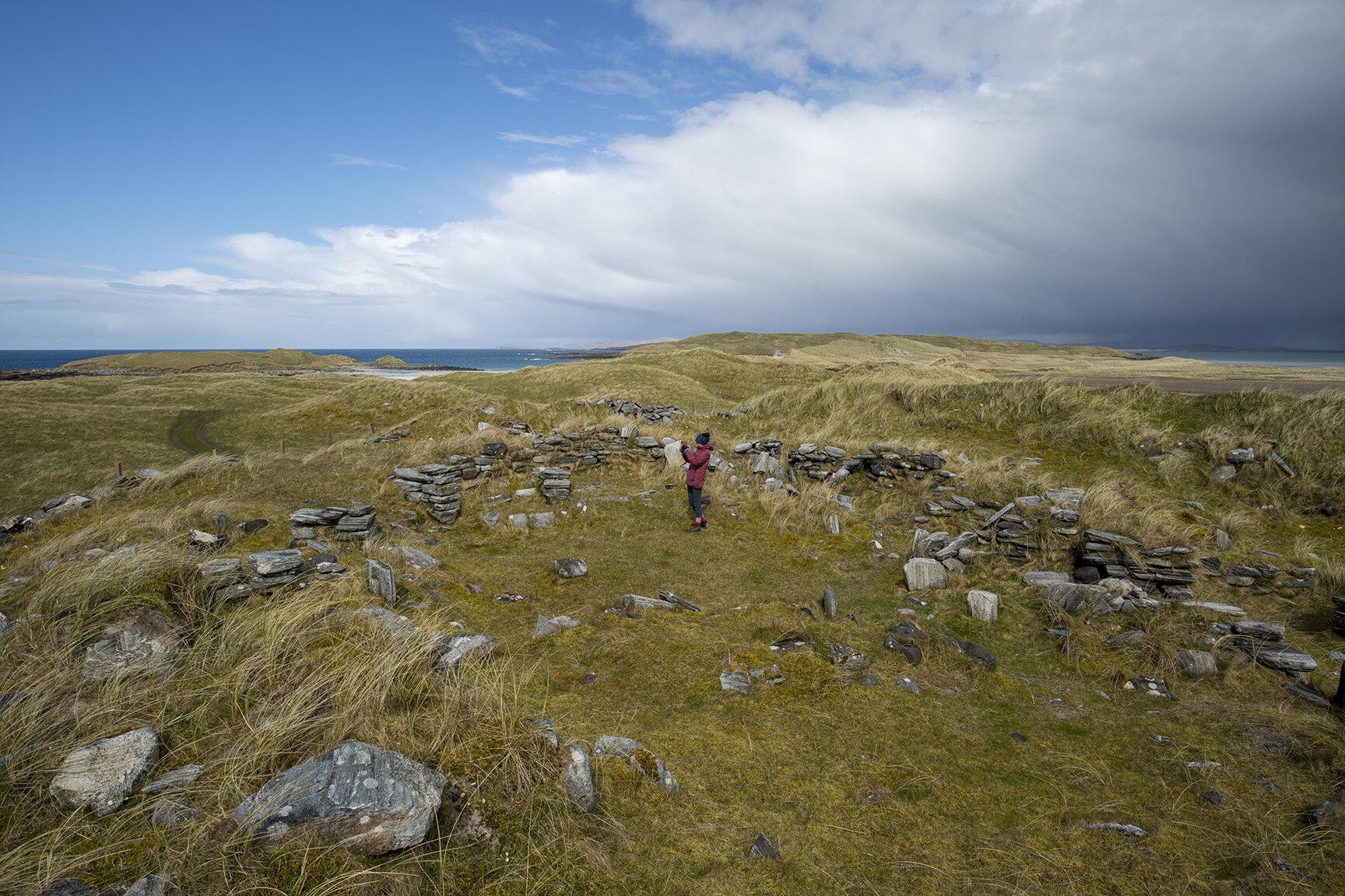 Kate within the wheelhouse archaeological site on Udal peninsula.