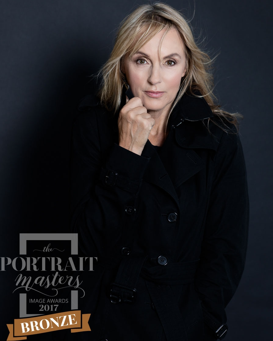 Portrait of a women over 50 with long blond hair, wearing a black Burberry Mac Coat facing the camera with a strong attitude. Step into your power!You are powerful, you are you, make the most of it. Another portrait awarded Bronze by the Portraits Masters.