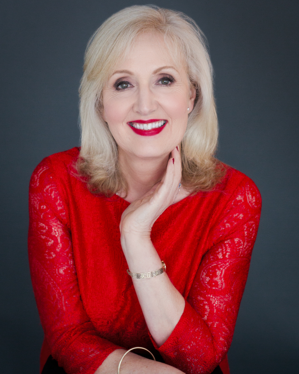 Portrait of an elegant woman over 60, wearing a red dress, facing the camera, shot in the studio. A lady in Red.Step into your power and you are!