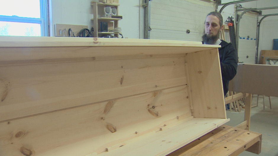 Carpenter Jeremy Burrill has designed a casket that he says anyone can assemble. (CBC )
