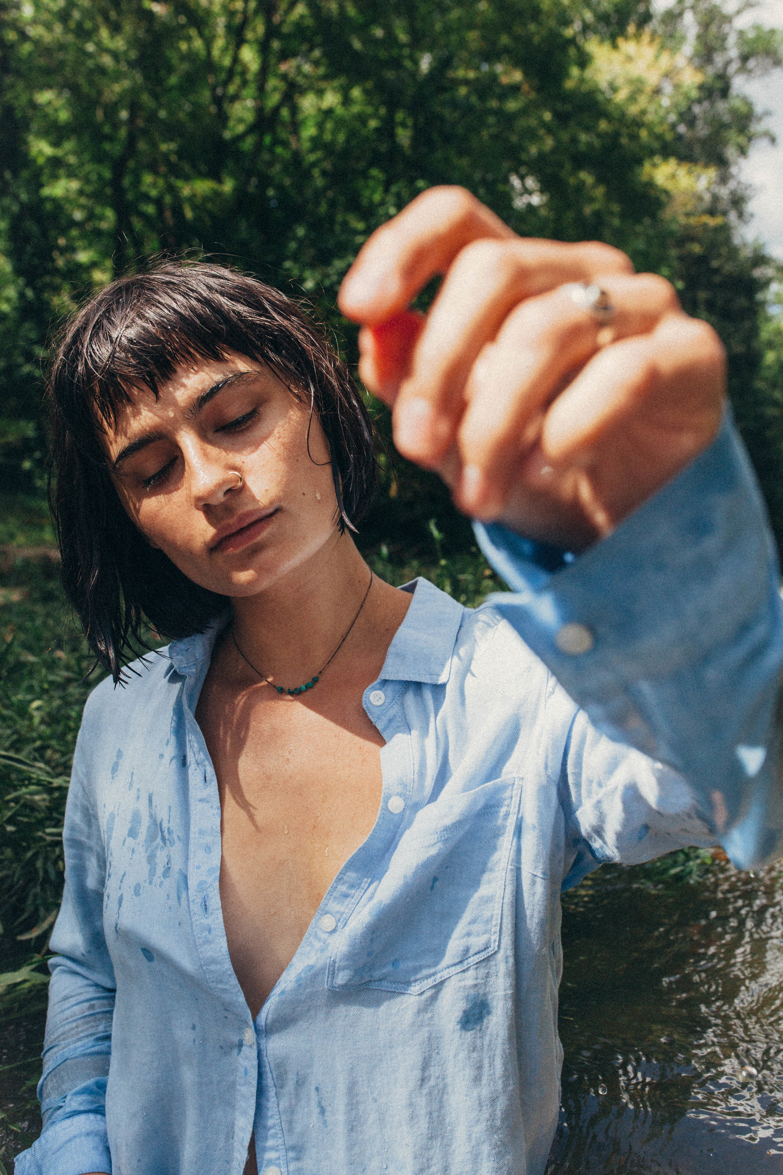 portrait of a dark haired girl in a blue button up in the river in Missouri