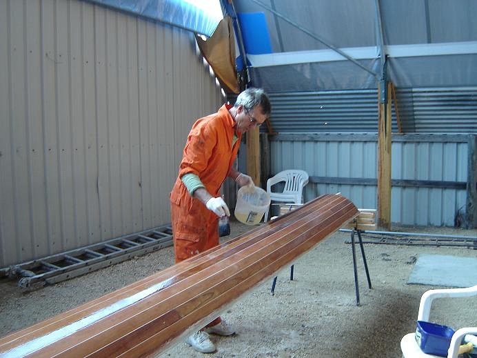 Kit Stage 1. Forebeam, Dagger Boards and Cases.  Here John is resin coating the strip planked forebeam in preparation for the fiberglass laminating schedule.  March-September 2009.