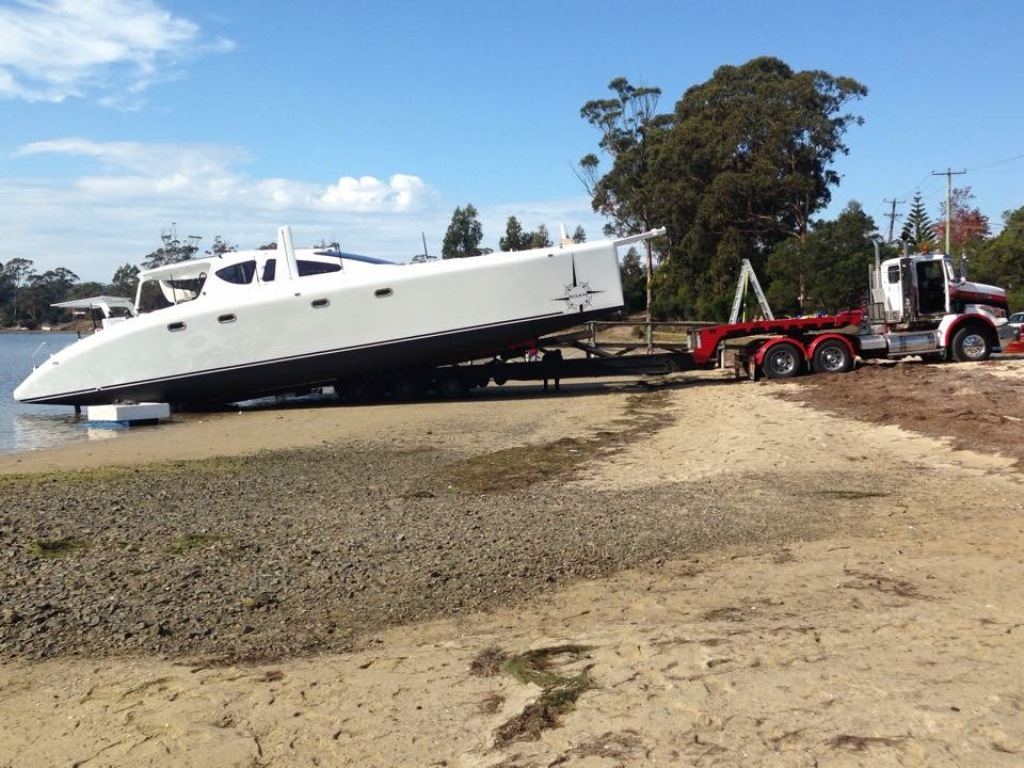 "ROAM was launched without crane using Kellara Trasport's ""tilt-slide"" trailer.  The small tides that exist on Tasmania's East Coast meant that the operation had to occur at the peak of the monthly tide cycle.  Timing and placement of the boat on the beach was critical.  April 2015."