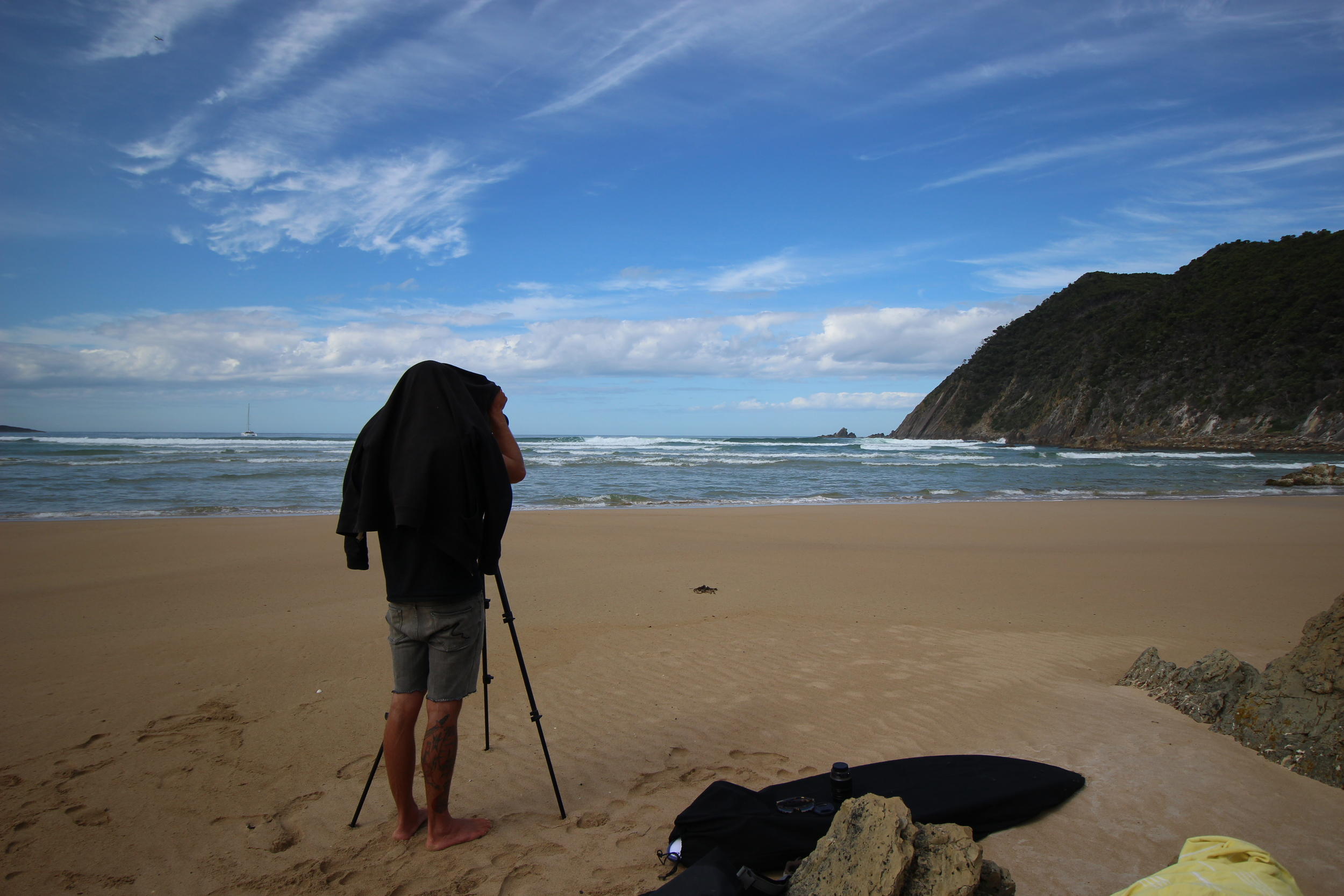 Andy setting up the camera at Surprise Bay to capture some surf footage at this remote break. Roam in the back ground.