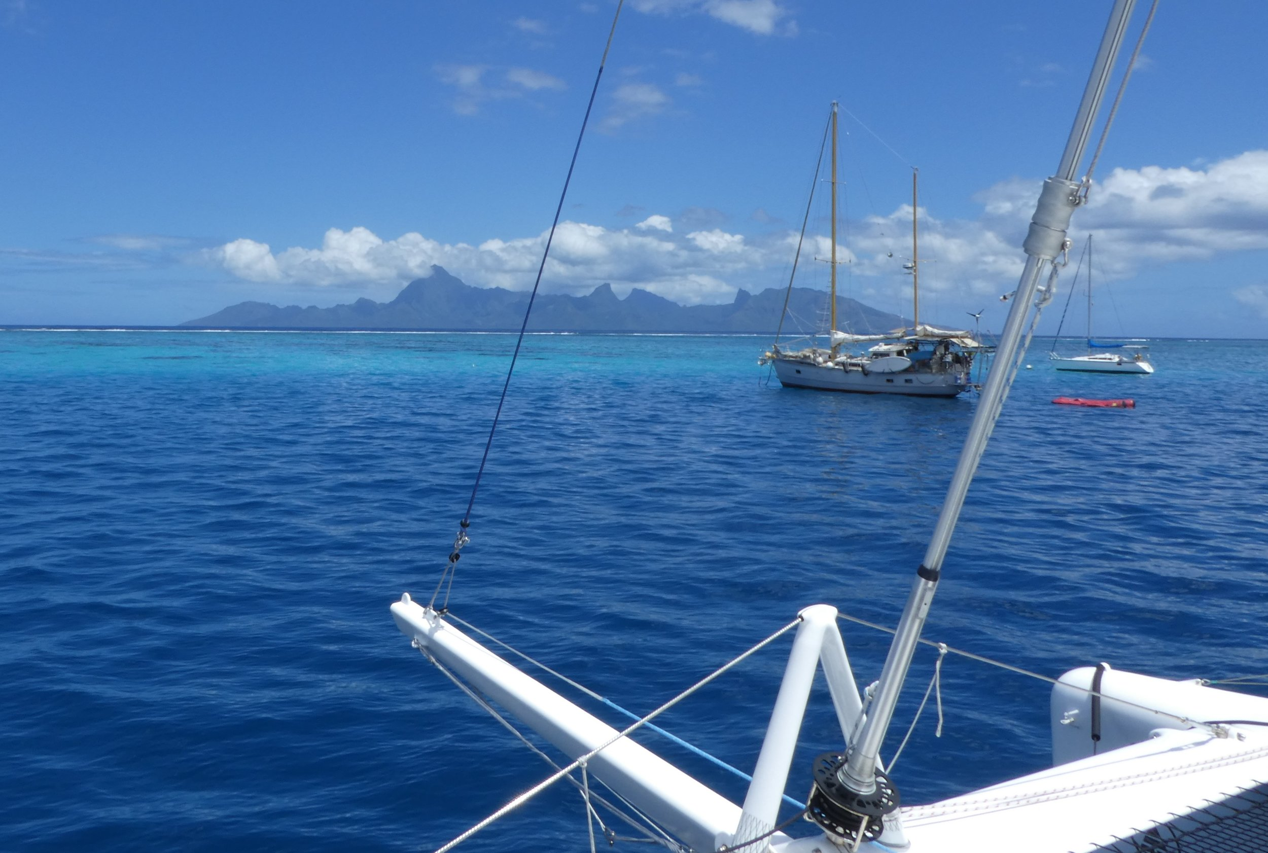 Roam, moored off Papeete, Moorea in the distance