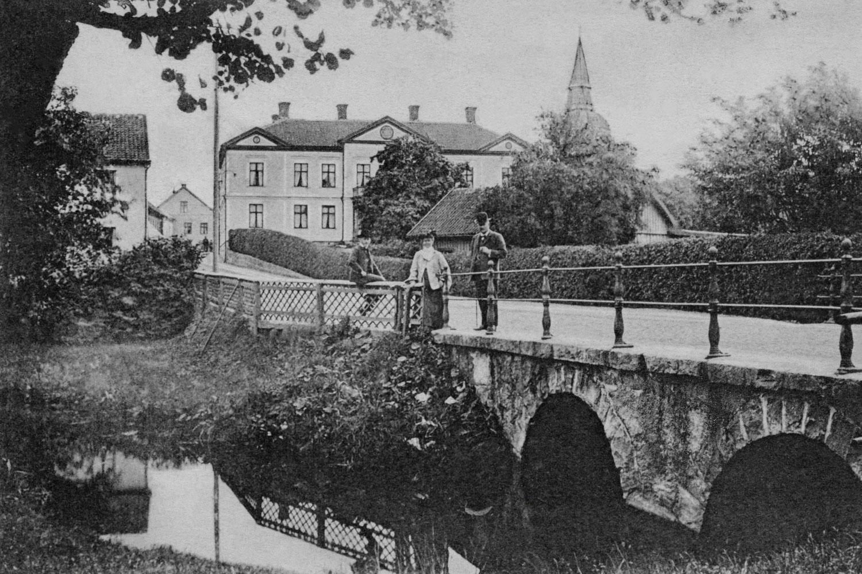 Kan det vara familjen Röhss som paraderar på Norrbro? Lägg märke till Karl XII:s stuga vars tak sticker upp i grönskan. Den fick sitt namn efter berättelsen om att Karl XII lutade sig mot huset och vilade i väntan på att bli överskeppad till Östergötland.