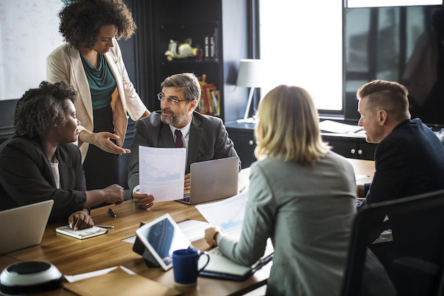 multi-racial group of women meet with white men in business setting