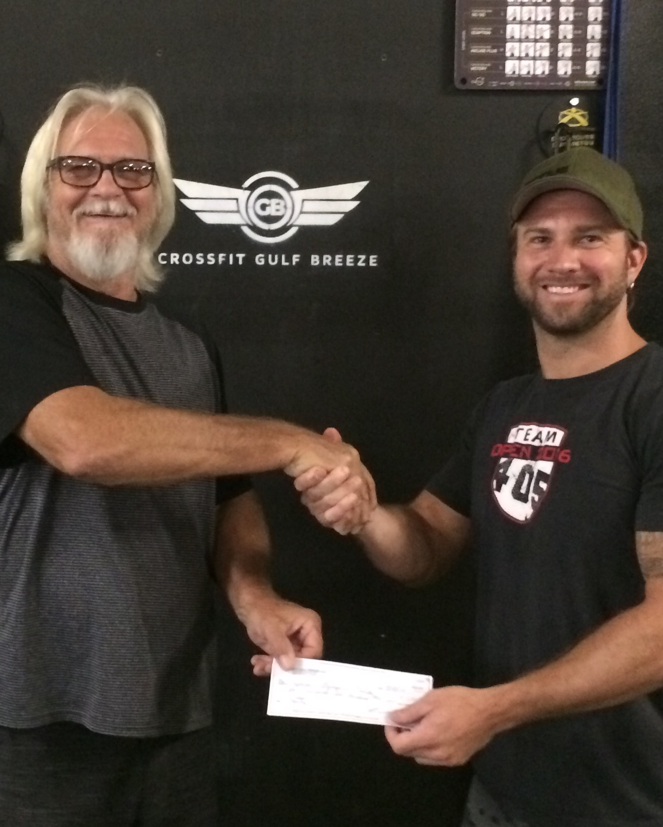Michael Stone (the Director of Escambia and Santa Rosa Counties of Special Olympics Florida) receiving the donation check from Jarett Venn (owner of CFGB).
