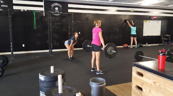 Coach Ginger making sure one of our Beginner CrossFit members has proper form while deadlifting.