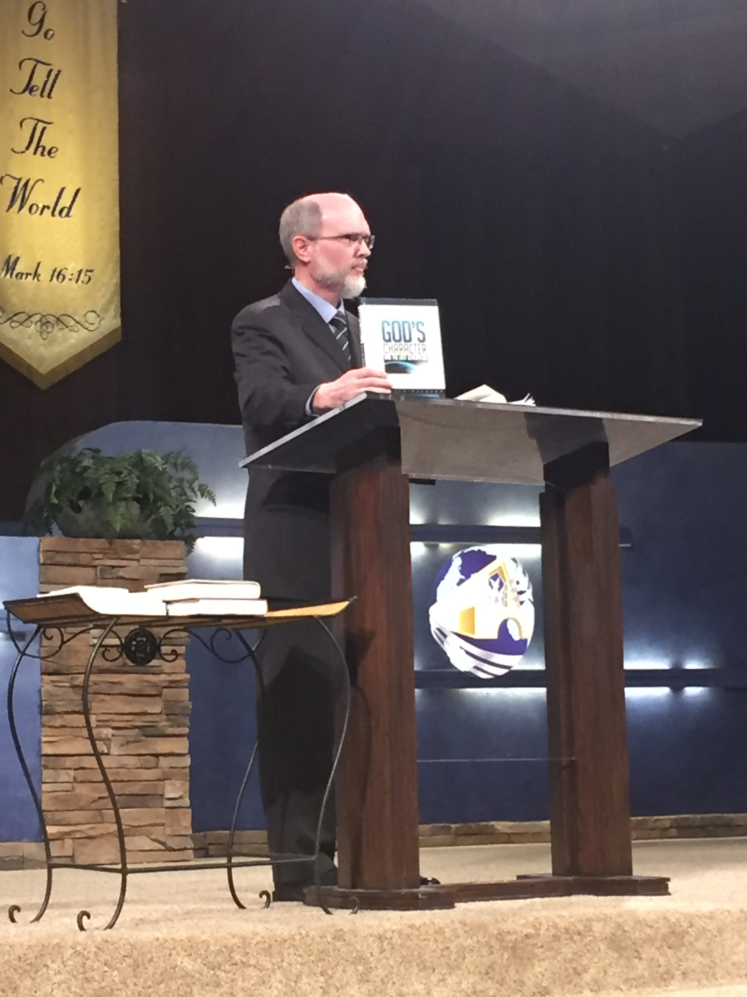 """Pastor Kirkpatrick holding the book under review, """"God's Character and the Last Generation"""" written by several Andrews University professors."""