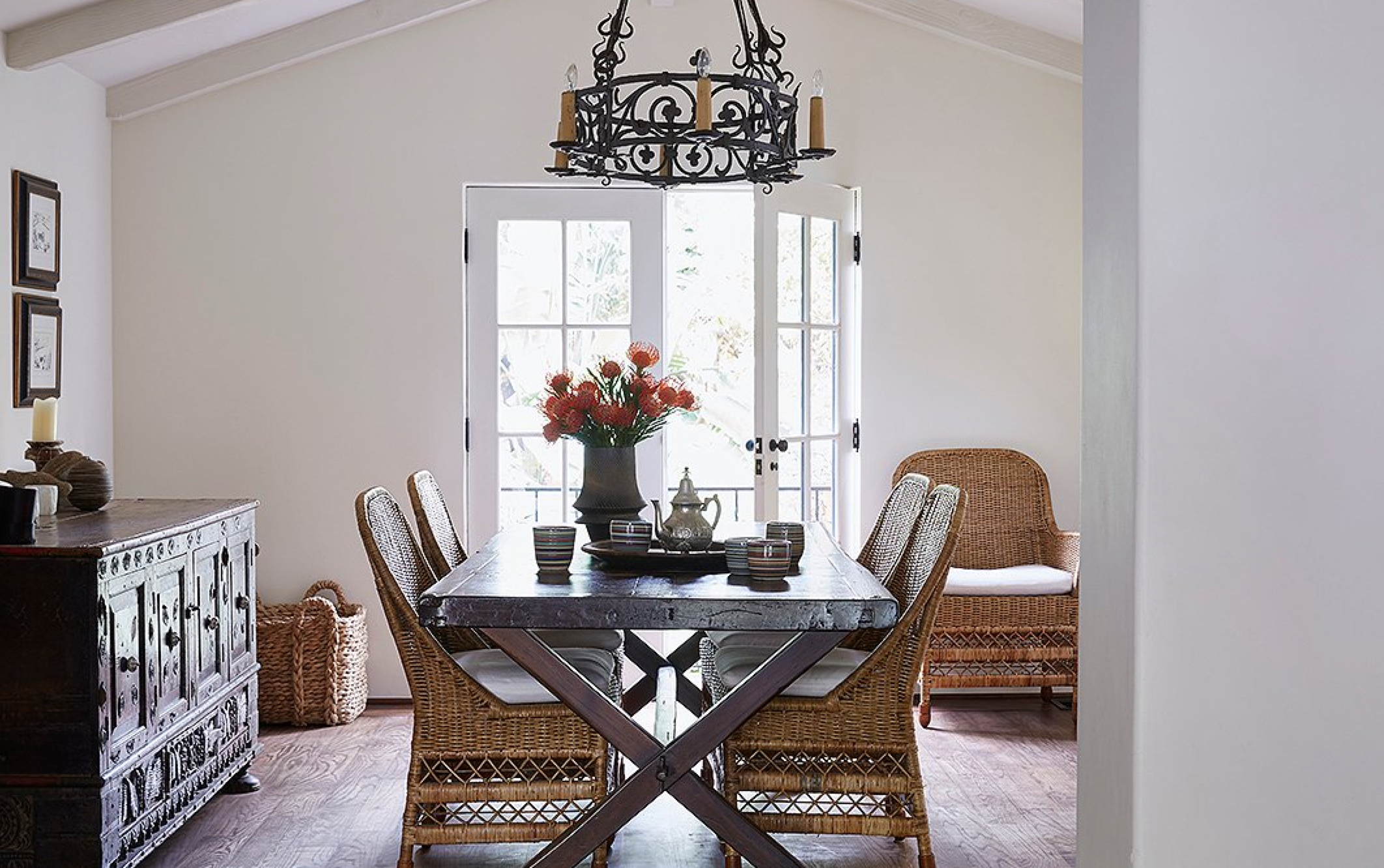 """This is the family table,"" says Kendall. ""We have dinner, the girls do their homework."" It was reimagined from an antique Spanish door. The rattan chairs add airy space. A vase by potter Miri Mara sits near striped cups by a local artisan."