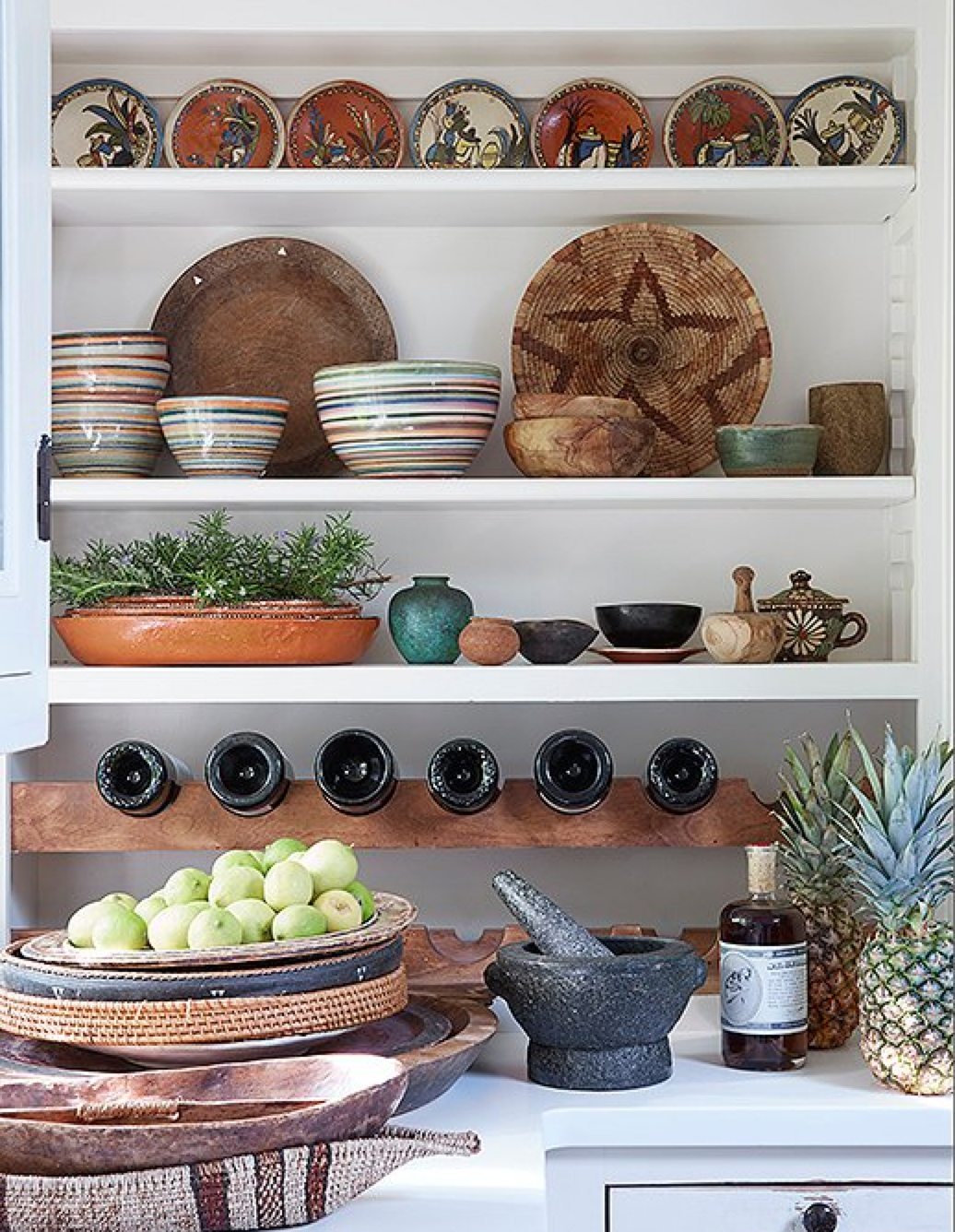 "Shelving in the kitchen shows off Kendall's love of global earthenware. ""The pieces are from all over,"" says Kendall. ""Plates from Mexico, a pre-Columbian pot, trays from Fiji. The rosemary and lemon are from our garden. I eat a lot of pineapple, but I also love the way they look on a counter."""