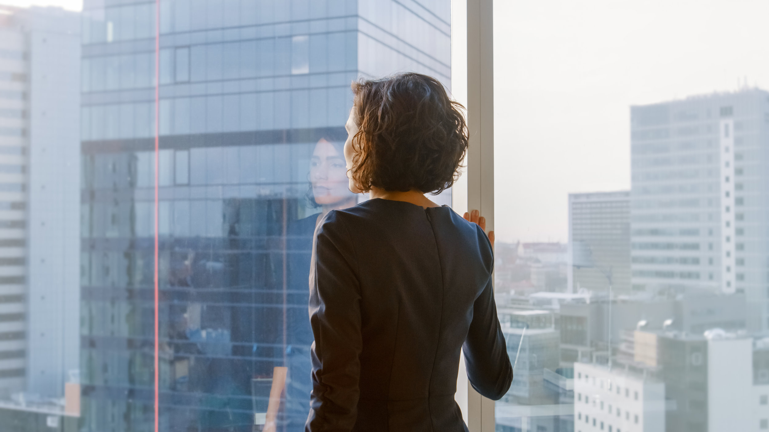 Shot-of-the-Successful-Businesswoman-in-a-Stylish-Dress-in-Her-Office-Looking-out-of-the-Window-Thoughtfully.-Modern-Business-Office-with-Personal-Computer-and-Big-City-View.-1069160082_5120x2880.jpeg