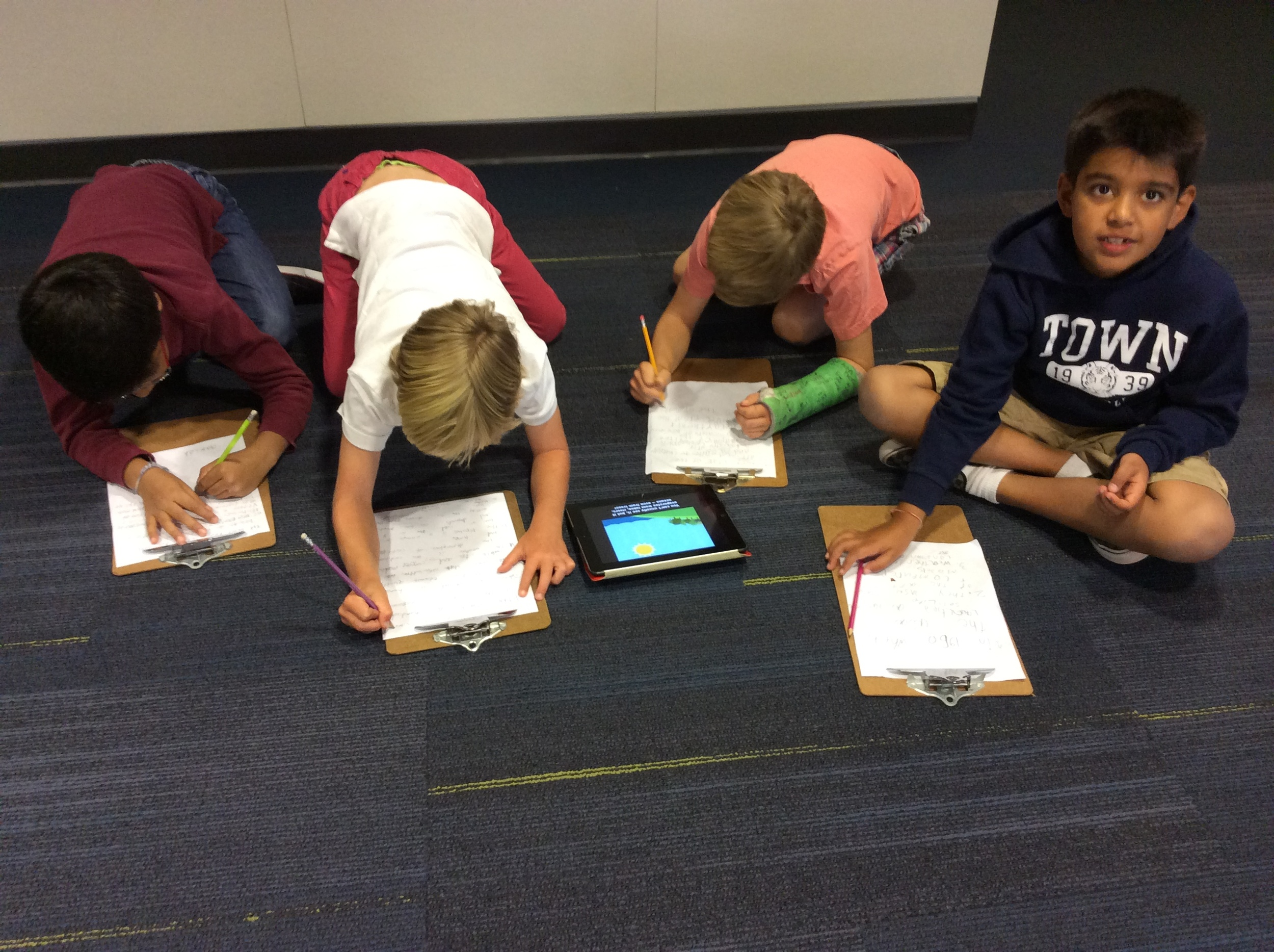In groups, boys are gathering more information from selected reading and videos.