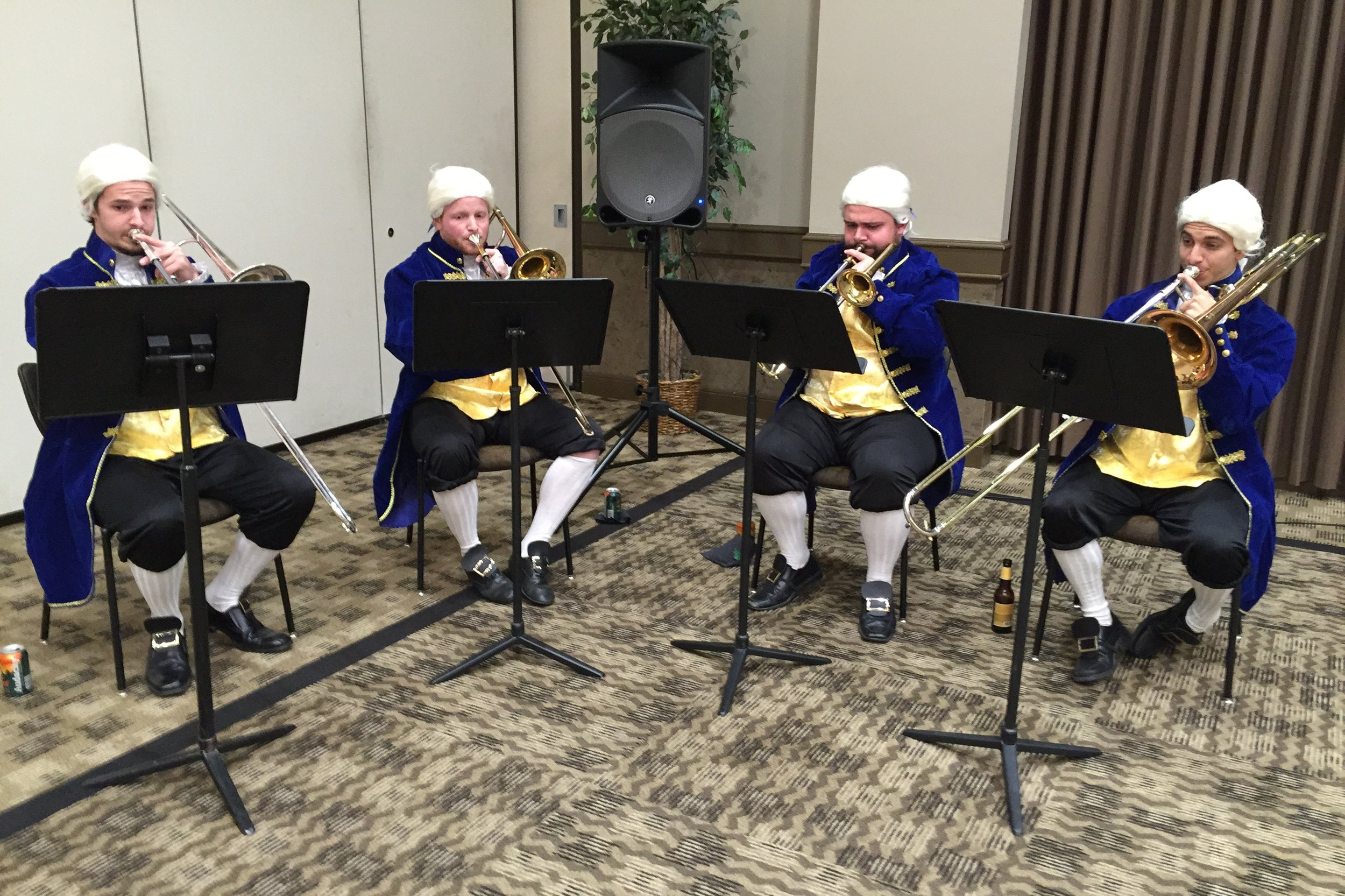UNT College of Music Trombone quartet dressed in period costume and powdered wigs perform Moravian brass music from the American Colonies during pre-dinner reception.