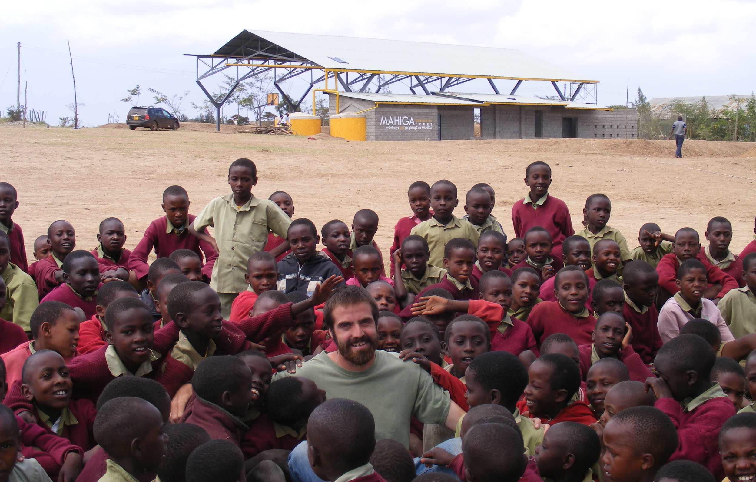 Greg is surrounded by a mob of children in front of the recently constructed Mahiga Rainwater Court (2010)