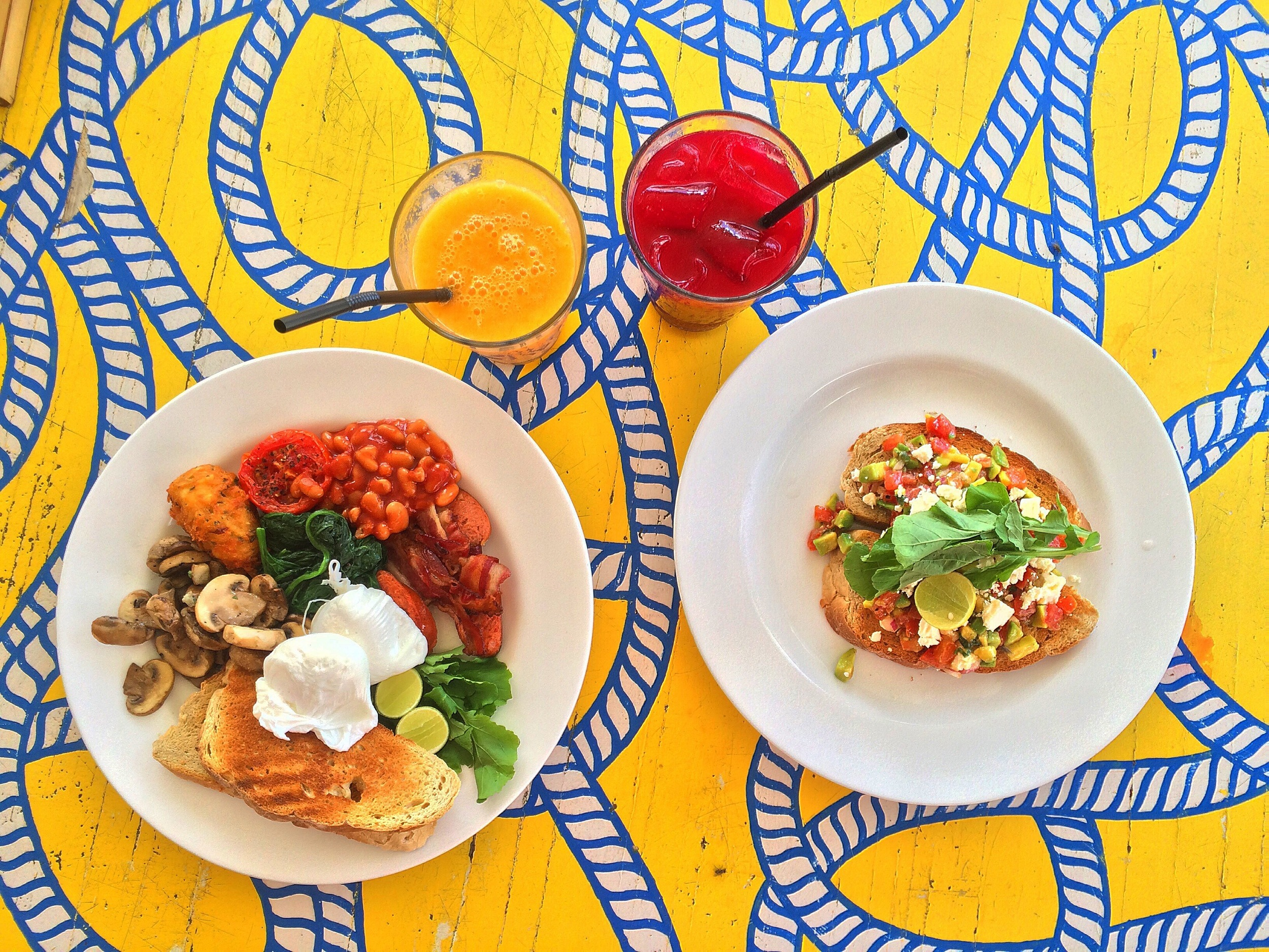 Two poached eggs, bacon, pork chorizo, spinach, mushrooms, roasted tomatoes, beans, hashbrown and a toasted sourdough slice and an open-faced avocado tomato salsa & feta on toasted sourdough sandwich.Plus, two refreshing juices to wash it all down!