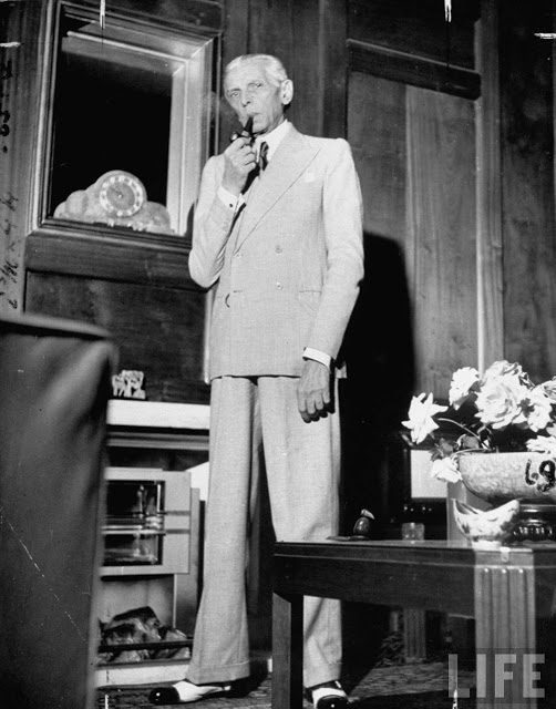 Portrait of Mohammed Ali Jinnah, Pres. of India's Moslem League, w. pipe in his mouth, dressed in Western-style suit, in the study of his palacial home - May 1946