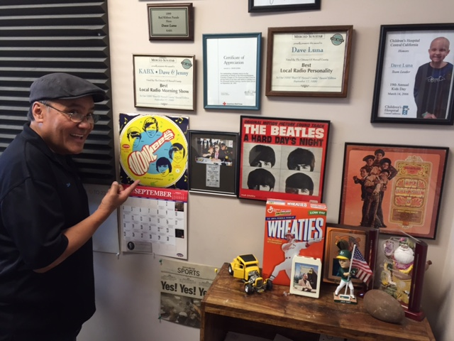 Dave Luna keeps rock and roll photos and vintage album covers on the studio wall at the Radio Merced offices on Main Street in Merced.  Photo by Steve Newvine