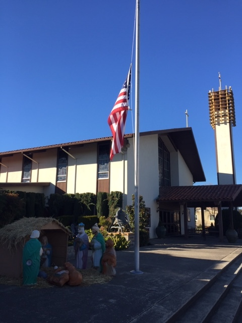 St. Joachim Catholic Church on Main Street in Newman, Stanislaus County. Like many properties displaying American flags in Newman, the flag in front of the Church is flying at half-staff in honor of Police Corporal Ronil Singh. Photo- Steve Newvine