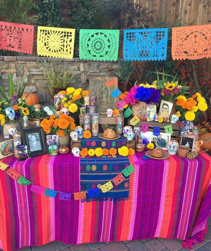 The bright tablecloth,   papel picado  , and vibrant flowers really bring this altar to life! Photo courtesy of Casa Artelexia.