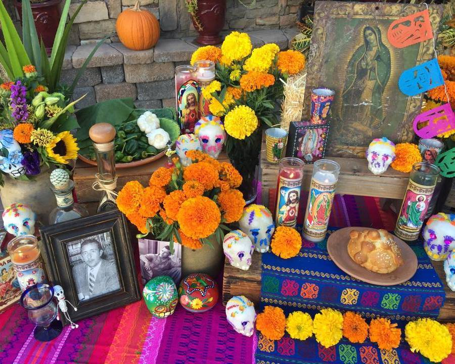 Black-and-white photos, a few bottles of tequila,   pan de muerto   (Day of the Dead bread), colorful   calaveras   (sugar skulls), and   veladora   candles add a special touch to this altar. Photo courtesy of Casa Artelexia.