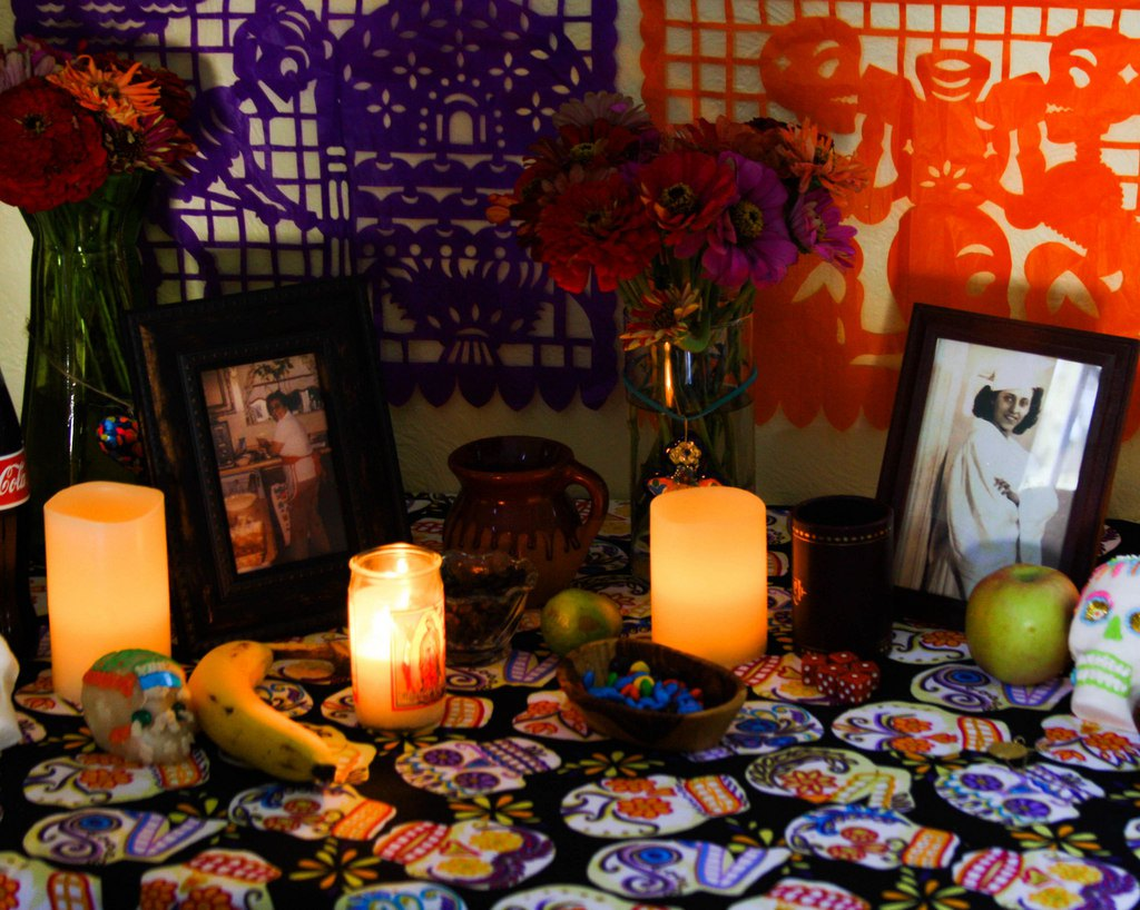 Nicole's altar includes homegrown zinnia flowers, Day of the Dead food-themed   papel picado  , and photos of her grandmother — one from her graduation because she loved to study, and the other in the kitchen, which shows her love for entertaining and baking. Photo courtesy of Flan and Apple Pie.