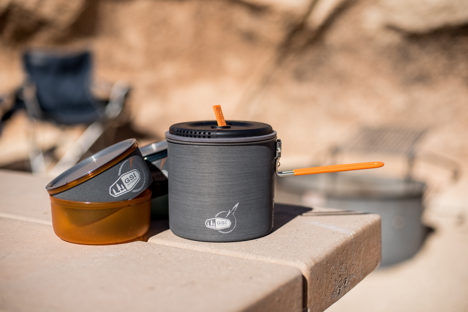 A cup and a bowl, with cozy cover, and the pot with handle out.