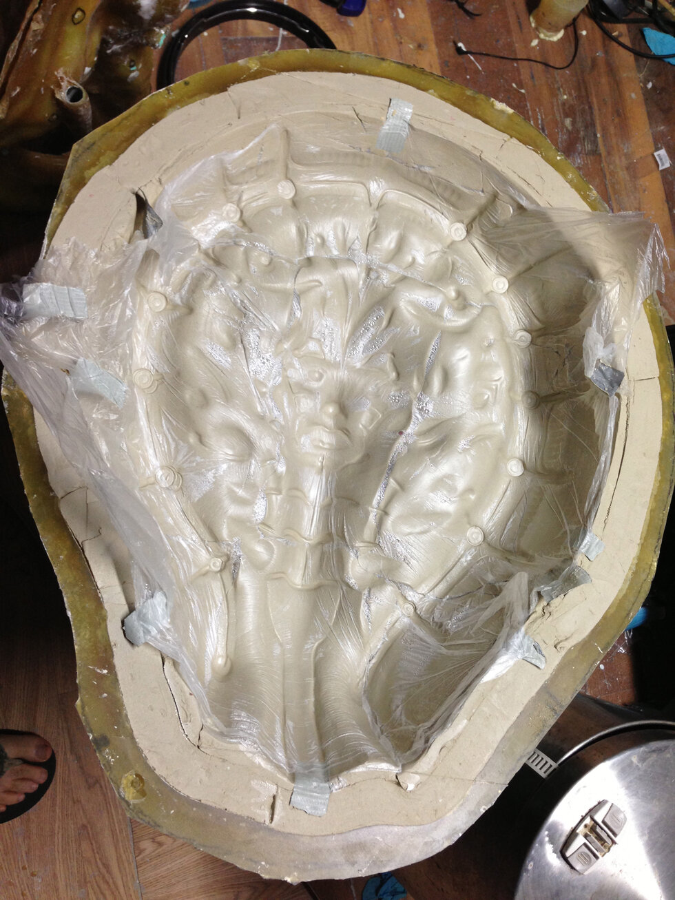 """Here is the fiberglass jacket popped of revalin gthe 3/8"""" layer of clay between the sculpture and the outer jacket. Once I pulled this out the jacket was carefully placed back on top of the sculpture and sealed down. Then liquid green silicone was poured into the new cavity. Once the silicone set in about 16 hours, presto, the first mold was born!"""