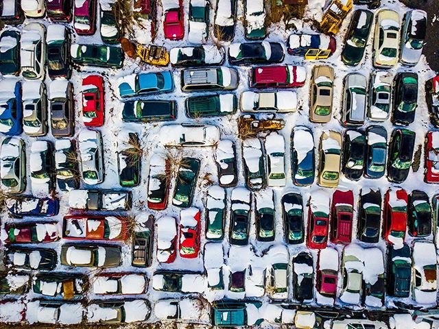A patchwork maze of frosted vehicles await dismantling.