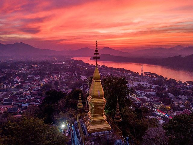Rose colored streaks paint the heavens above a sacred Laotian hill.