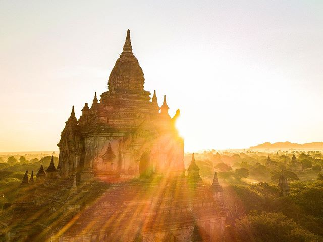 The sun rises above a temple's tower illuminating an expansive plain.